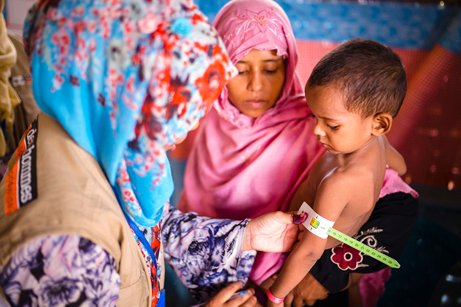 A Tdh staff screening a Rohingya refugee child on malnutrition